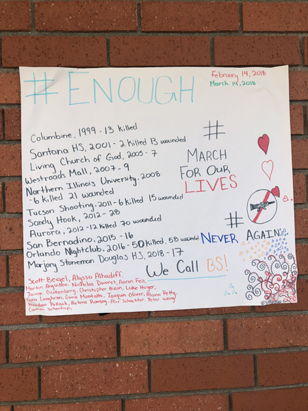 A poster made by senior Alana Carmona hangs on the wall during the #enough event.