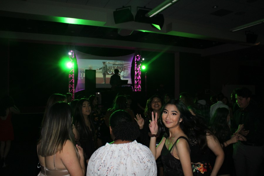 Students dancing under the green lights.